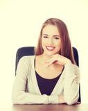 Belle femme s'asseyant par un bureau Image stock