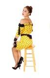Belle femme s'asseyant sur la chaise Photographie stock