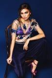 Belle femme s'asseyant sur la chaise dans le soutien-gorge bleu et le dessus floral Photo stock