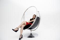 Belle femme s'asseyant sur la chaise sur le fond blanc Photographie stock libre de droits