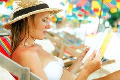 Belle femme s'asseyant sur la plage affichant un livre Photos stock