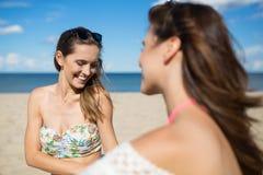 Belle femme s'asseyant sur la plage avec rire d'ami Photo stock