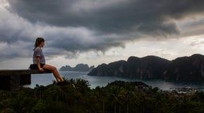Belle femme s'asseyant sur la plate-forme en bois avec les vues d'île de Phi Phi et le ciel nuageux images stock