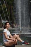 Belle femme s'asseyant sur le fond de fontaine Image libre de droits