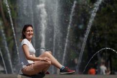 Belle femme s'asseyant sur le fond de fontaine Photos stock