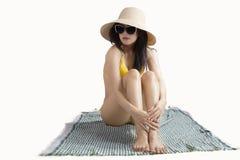Belle femme s'asseyant sur le tapis Photographie stock