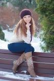 Belle femme s'asseyant sur un banc en hiver photo stock
