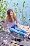 Belle femme s'asseyant sur un pilier au lac photographie stock