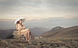 Belle femme s'asseyant sur une chaise Photographie stock