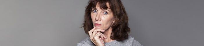 Belle femme 50s imaginative semblant sérieuse photos stock