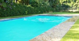 Belle femme sautant dans la piscine banque de vidéos