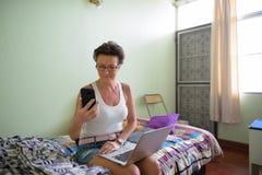 Belle femme scandinave mûre à l'aide du téléphone portable à la maison photo stock