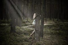 Belle femme se cachant derrière un arbre dans la forêt photo stock