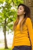 Belle femme se tenant contre l'arbre Photographie stock