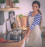 Belle femme se tenant dans la cuisine avec le tablier photographie stock