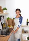 Belle femme se tenant dans la cuisine avec le tablier Image libre de droits