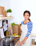 Belle femme se tenant dans la cuisine avec le tablier Photos libres de droits