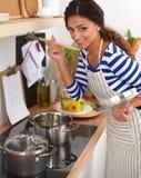 Belle femme se tenant dans la cuisine avec le tablier Photos stock