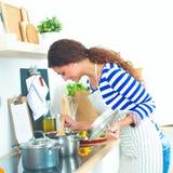 Belle femme se tenant dans la cuisine avec le tablier Photo libre de droits