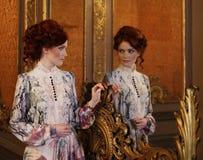 Belle femme se tenant dans la salle de palais avec le miroir Images libres de droits
