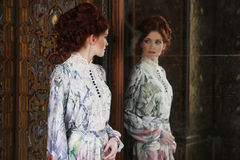 Belle femme se tenant dans la salle de palais avec le miroir Images stock