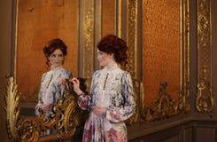 Belle femme se tenant dans la salle de palais avec le miroir photos libres de droits