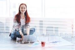 Belle femme semblant heureuse tout en travaillant dans son bureau Photographie stock libre de droits