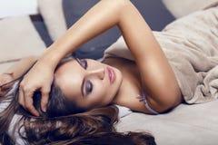 Belle femme sensuelle avec de longs cheveux foncés dans le plaid se trouvant sur le divan Images stock