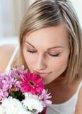 Belle femme sentant un groupe de fleurs images libres de droits