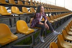 Belle femme seule s'asseyant sur des tribunes et des regards de côté Photo libre de droits