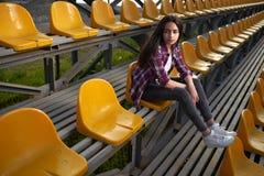 Belle femme seule s'asseyant sur des tribunes et des regards de côté Photo stock