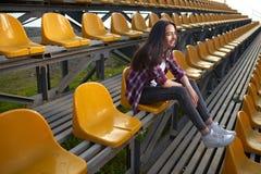 Belle femme seule s'asseyant sur des tribunes et des rires Photographie stock libre de droits