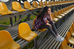 Belle femme seule s'asseyant sur des tribunes et des sourires Photographie stock libre de droits
