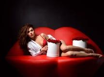 Belle femme sexy à la mode de luxe se trouvant sur le sofa rouge c de lèvres images stock
