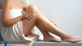 Belle femme sexy avec de longues jambes détendant en serviette de bain après s'être baigné photos stock