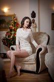Belle femme sexy avec l'arbre de Noël à l'arrière-plan se reposant sur la chaise élégante dans le paysage confortable Portrait de Photo stock