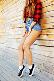 Belle femme sexy dans des shorts et des espadrilles de jeans Lifesty extérieur Image libre de droits