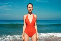 Belle femme sexy dans des v?tements de bain rouges sur la plage photo stock