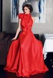 Belle femme dans la longue robe de soirée rouge de la soie Photographie stock