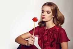 Belle femme sexy dans la robe en soie avec des lèvres de sucrerie sur le bâton Photographie stock libre de droits