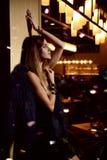Belle femme sexy de brune de mode dans le restaurant intérieur cher avec des plantes tropicales image libre de droits