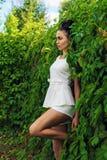 Belle femme sexy se tenant près d'une bordure de haies verte image libre de droits