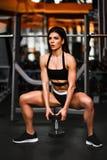 Belle femme sexy sportive faisant la s?ance d'entra?nement accroupie dans le gymnase photo stock