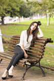 Belle femme songeuse et élégante s'asseyant sur le vieux banc Photos libres de droits