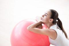 Belle femme songeuse reposant ses mains sur une boule de forme physique Photographie stock