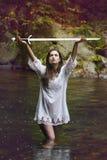 Belle femme soulevant une épée au ciel Images stock