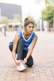 Belle femme sportive attachant ses chaussures avant l'exercice et le t image stock