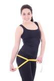 Belle femme sportive mesurant ses hanches d'isolement sur le blanc images stock