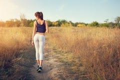 Belle femme sportive mince se tenant au coucher du soleil dans le domaine Photo stock