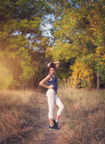 Belle femme sportive mince se tenant au coucher du soleil dans le domaine Photos libres de droits